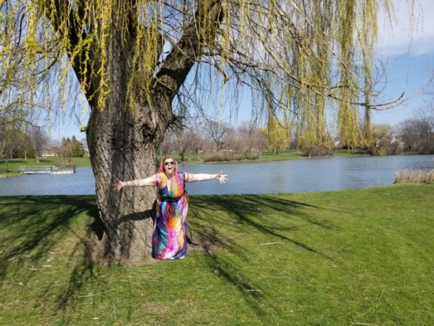 Chrissy wearing a brightly colored patterned dress in front of a willow tree and a lake