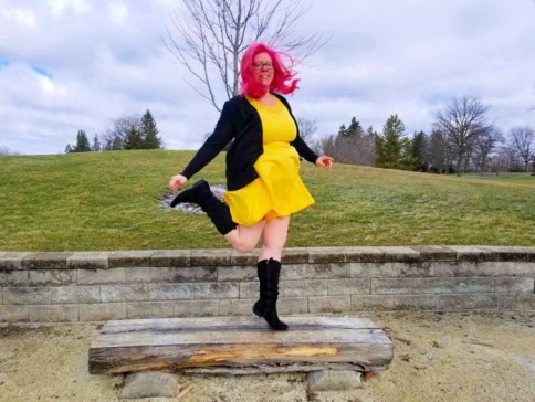Chrissy dancing on a bench with pink hair and a yellow dress
