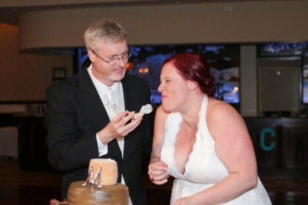 hilarious professional wedding photos  laughing while cutting the cheese wedding cake made of cheese wheels