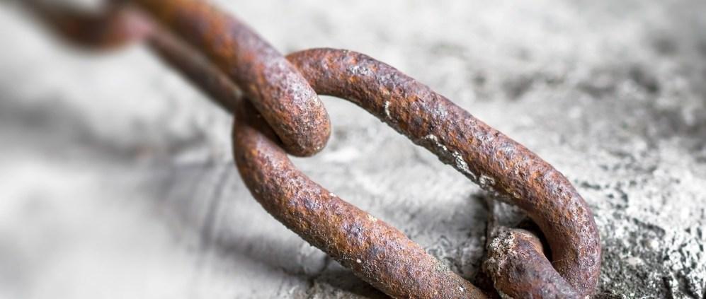 Rusty chain into the concrete