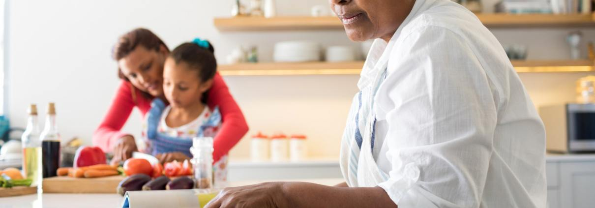 Senior woman looking at recipe book in kitchen