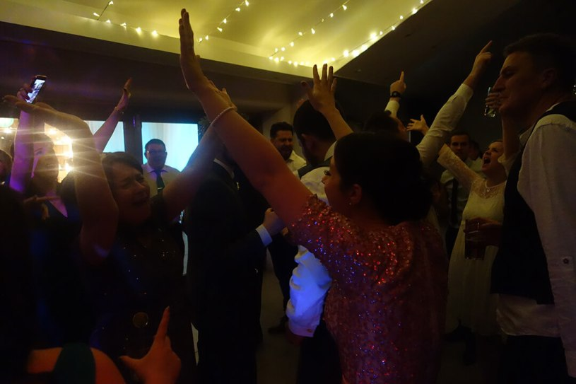 Wedding DJ making everyone put their hands in the air during the reception party at Trevenna, Cornwall
