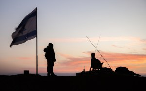 idf soldier stands next to tank by flag at sunset