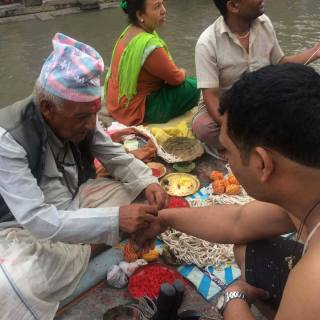 A Guru Brahmin binds are holy thread on wrist before giving him the holy thread for body known as Janai