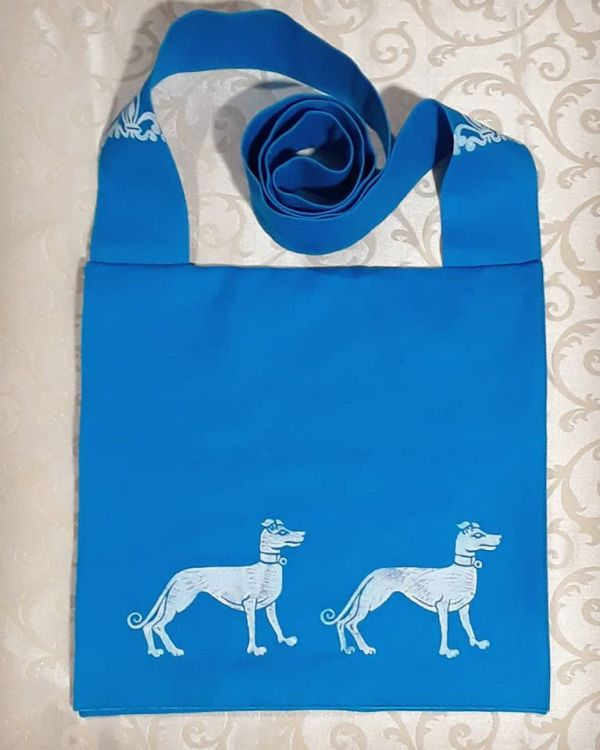 Turquoise bag handprinted with white 15th century inspired greyhounds.