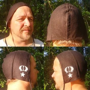 Large linen coif/arming cap made from lovely black linen fabric, handprinted in white with handcut stamps showing the Kingdom of Meridies populace badge.