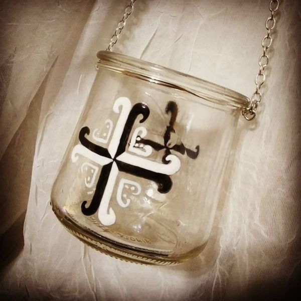 A lovely small upcycled hanging glass candle holder, made from a yoplait/oui glass jar, painted by hand with a black & white Meridian Cross.