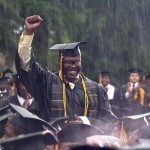 Graduate Frederick Anderson stands in the pouring rain as President Barack Obama acknowledges him during the Morehouse College 129th Commencement ceremony, Sunday, May 19, 2013, in Atlanta. (AP Photo/Carolyn Kaster)