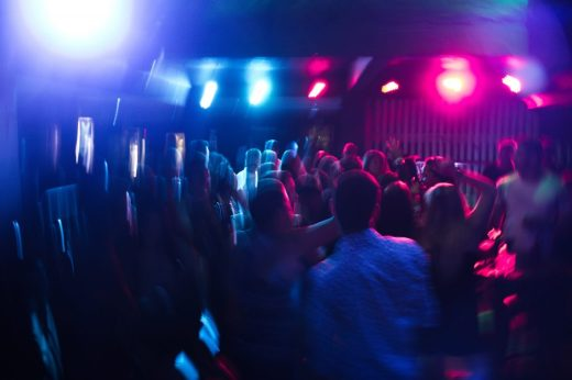 People dancing inside a building. Image is blurred, with dim lighting and light flares. Picture aims to depict the sensory overload experience of neurodiverse people.