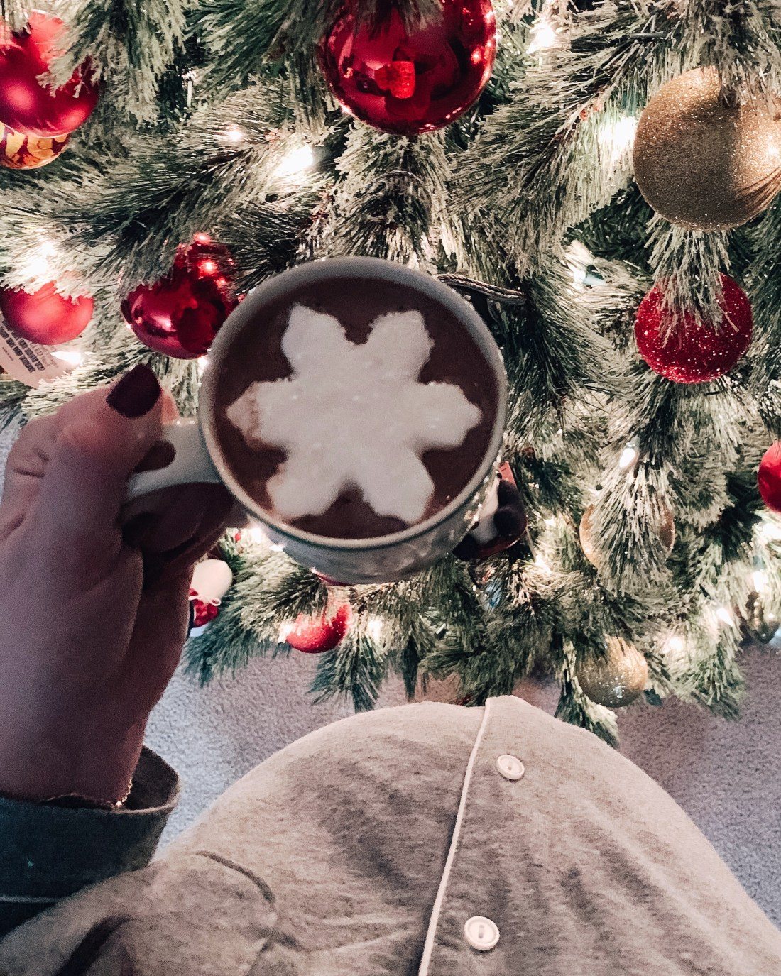 Pregnant Belly next to christmas tree and hot chocolate