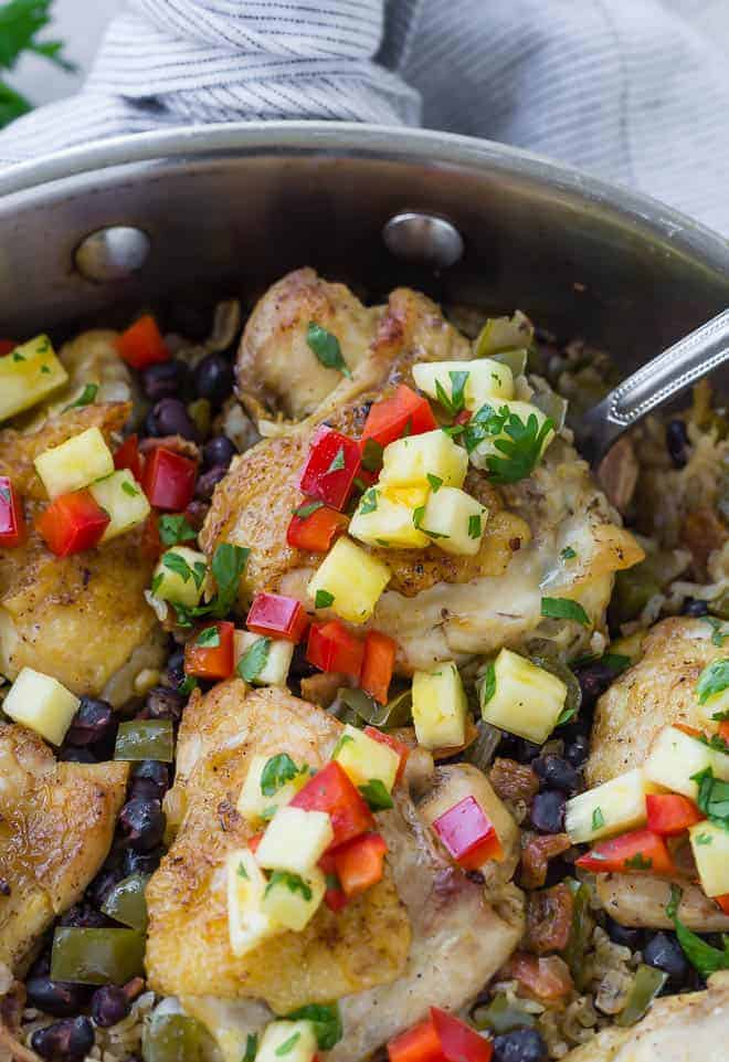 Tender, roasted chicken thighs nestled in a bed of rice, black beans, and peppers, gently seasoned with cumin and topped with a fresh pineapple salsa. I'm sure you'll love this one pan Cuban chicken and rice as much as I do!