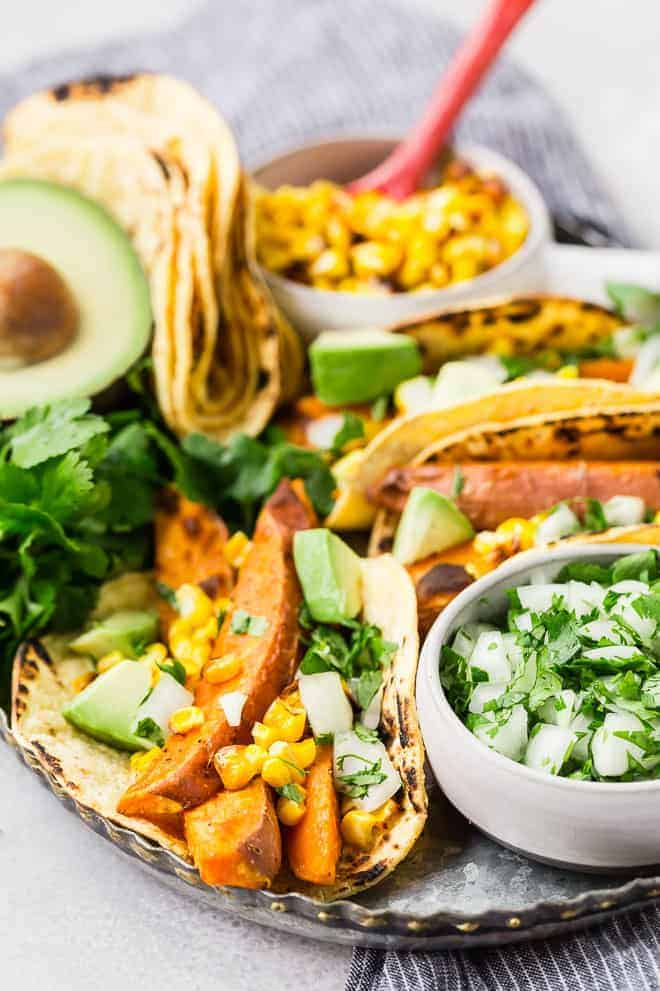 Beer marinated roasted sweet potatoes, charred corn, creamy avocado, crisp onions, and fresh cilantro, wrapped in a soft corn tortilla, make these vegetarian sweet potato tacos a taste sensation!
