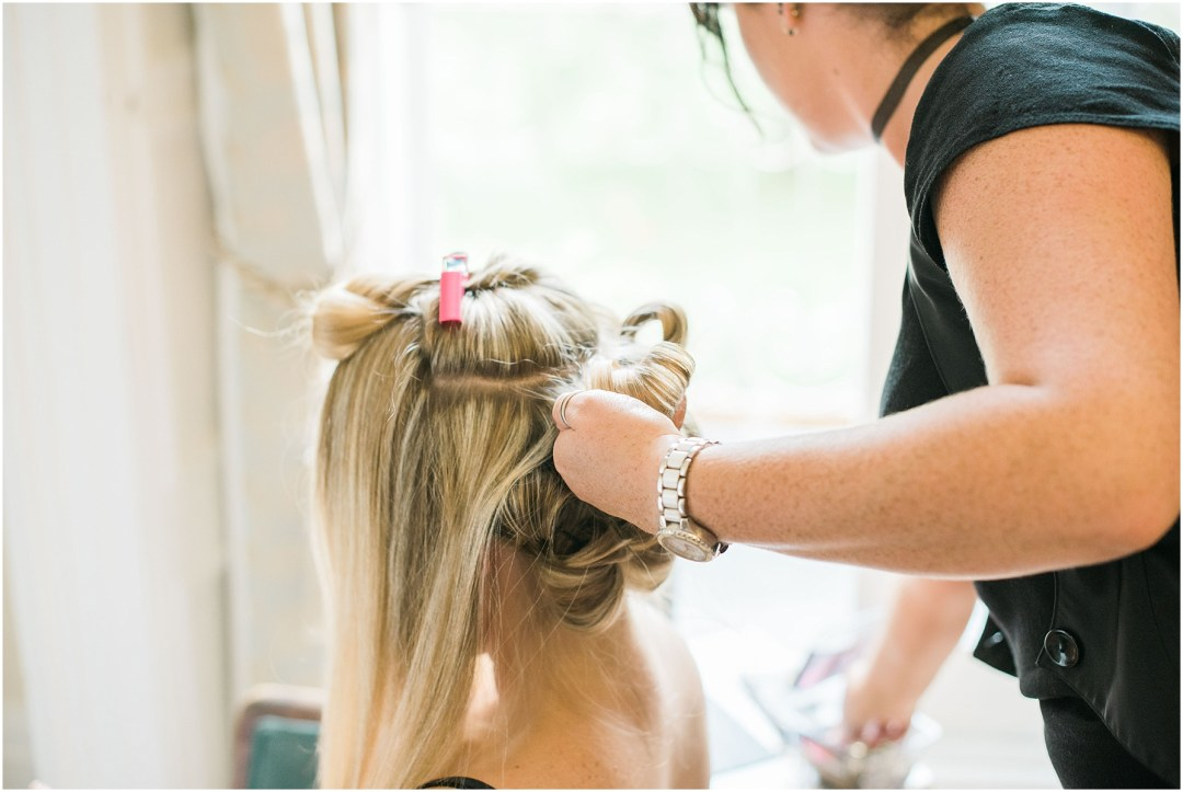 bridesmaid having her hair done during bridal prep at chiseldon house hotel