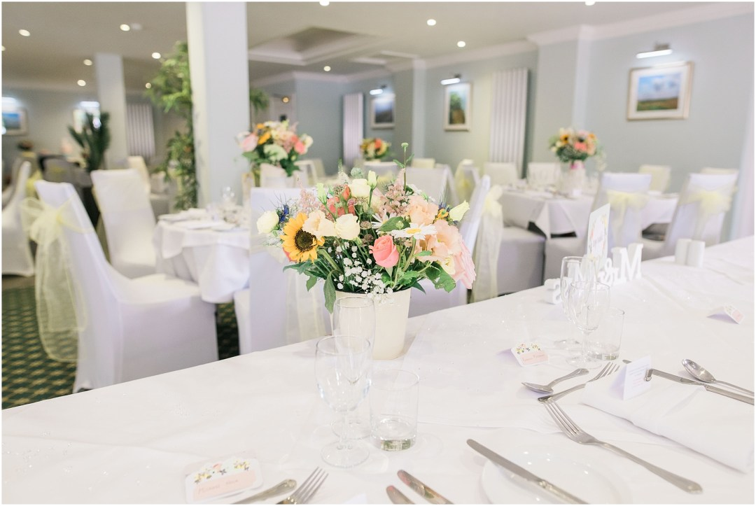 wedding breakfast table with pastel coloured flowers in cream jars