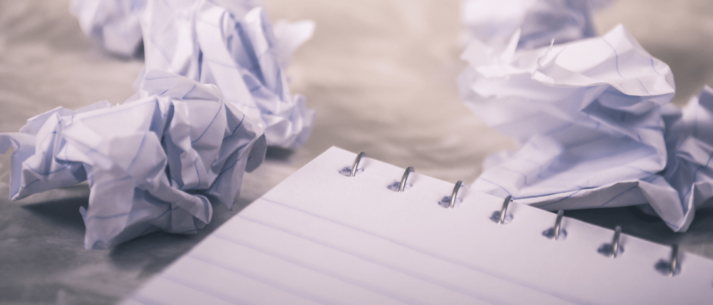 The top corner of a notebook, with a collection of discarded scrunched-up sheets of paper