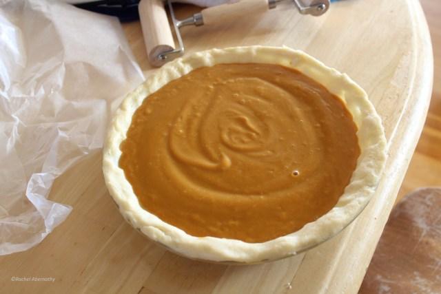 Raw butternut squash pie filling in the prepared pie crust.