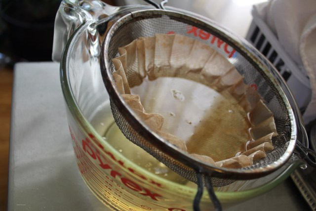 Straining hot lard through a coffee filter.
