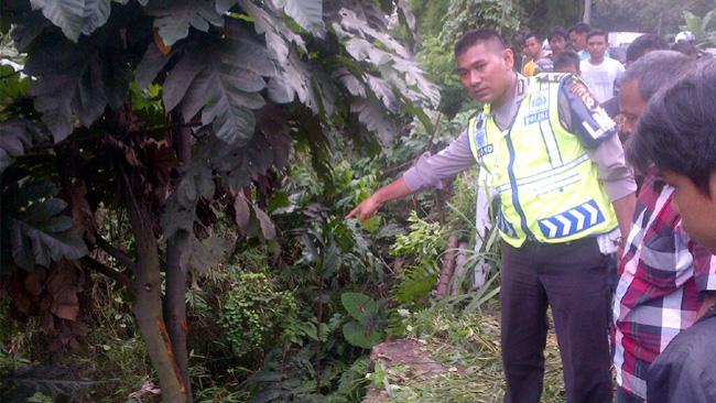 Salah seorang petugas menunjukkan lokasi jatuhnya kendaraan