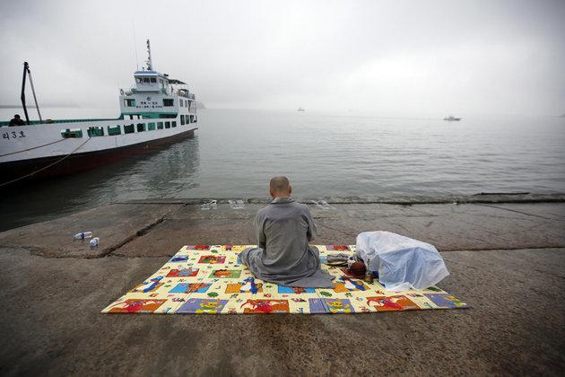 Un moine bouddhiste prie pour les disparus dans le naufrage © Reuters