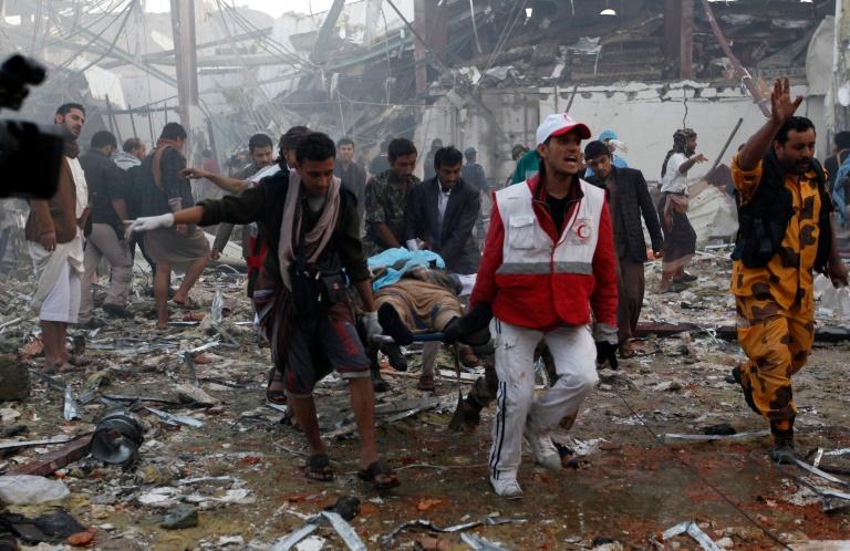 Des secouristes yéménites transportent un corps après des frappes attribuées à la coalition arabe à Sanaa, le 8 octobre 2016 . © AFP