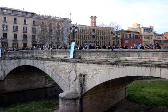 Omplen el riu Onyar, afluent del riu Ter, amb galledes d'aigua al Pont de Pedra de Girona