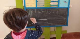 Nen escrivint en una pissarra d'escola | Imatge de l'Ajuntament de Palafrugell