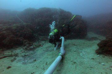 Un arqueòleg destapant les restes del vaixell de mitjans del segle I aC que s'ha descobert a les illes Formigues. Imatge cedida el 18 de novembre del 2020 (Horitzontal)