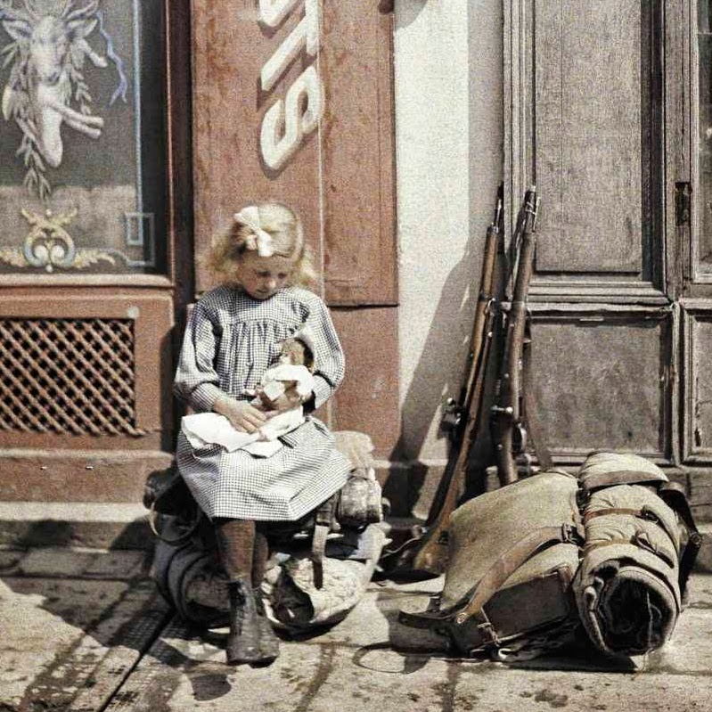 1917 Fernand Cuville, A little girl playing with her doll; two guns and a knapsack are next to her on the ground, Reims copy