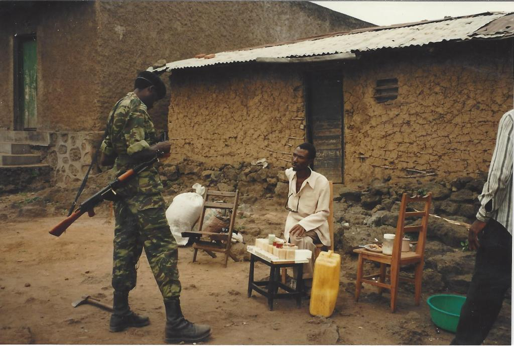 Zairean soldier checking the ID of a refugee selling soap