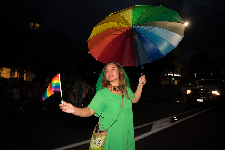 Marama Davidson rocking a rainbow umbrella