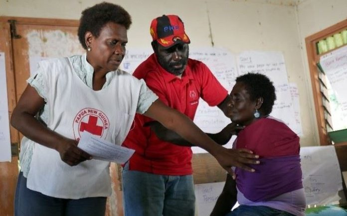 PNG Red Cross Bougainville branch coordinator Aidah Kenneth (left) demonstrates how to stabilize an arm fracture, with the help of first aid trainers Pais Tawoanea (center) and Benedine Siunai (right).