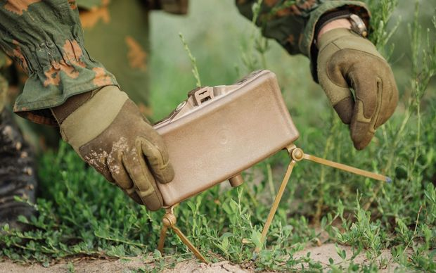 A solider planting a land mine.