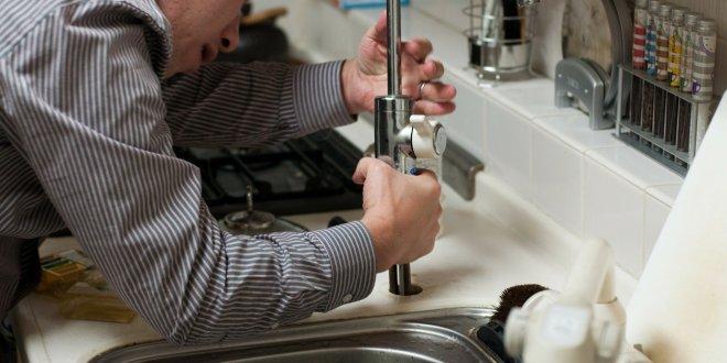 Plombier en train de démonter un robinet sur un évier.