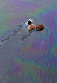 Resident of New Orleans, swimming in oil-slicked water. Source: Bill Haber/AP