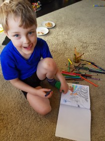 Boy-doodling-in-a-coloring-book