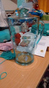 This photo contains a clear melamine pitcher, lidded, on a messy desk