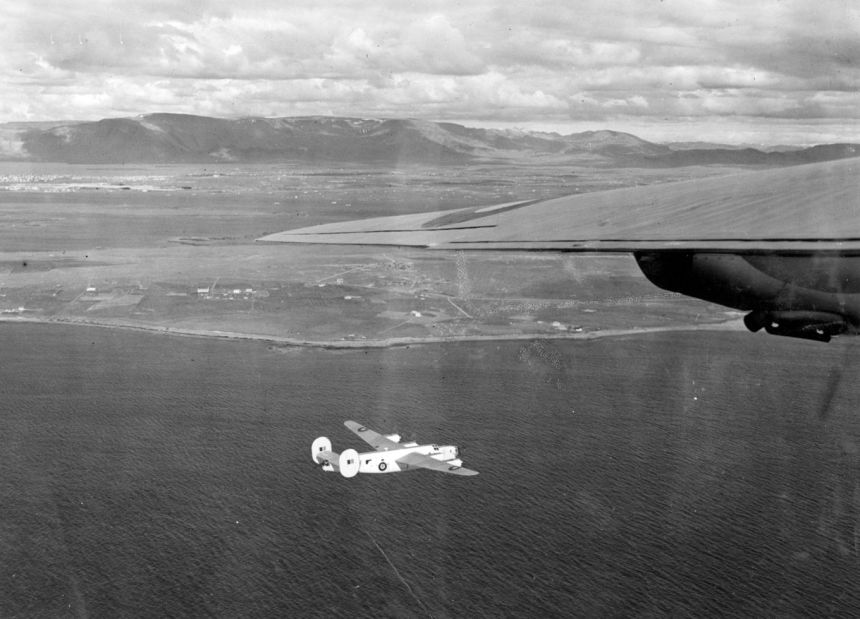 A black and white image showing Consolidated Liberator GR.IIIs flying over the sea.