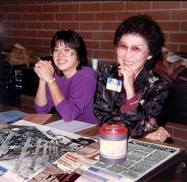 Lillian Nakano and June Hibino at an information table during a redress-related event in the 1980s.