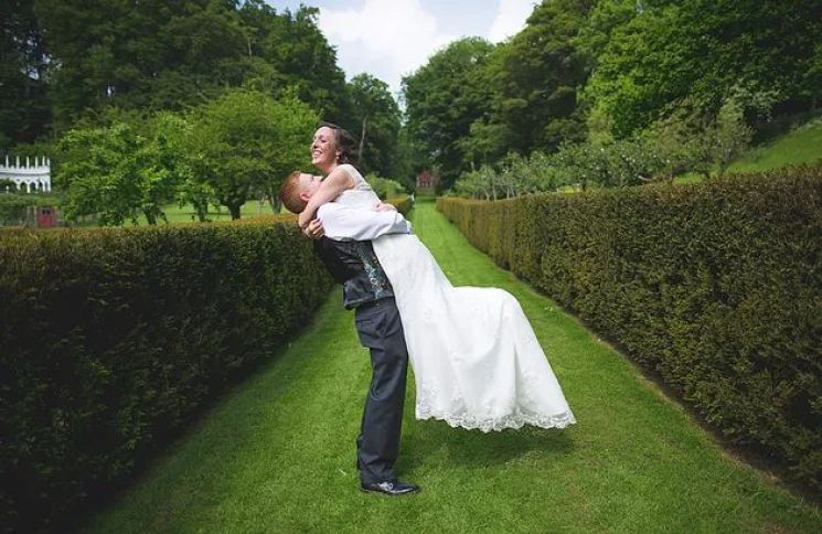 Groom lifting his bride up at Painswick gardens
