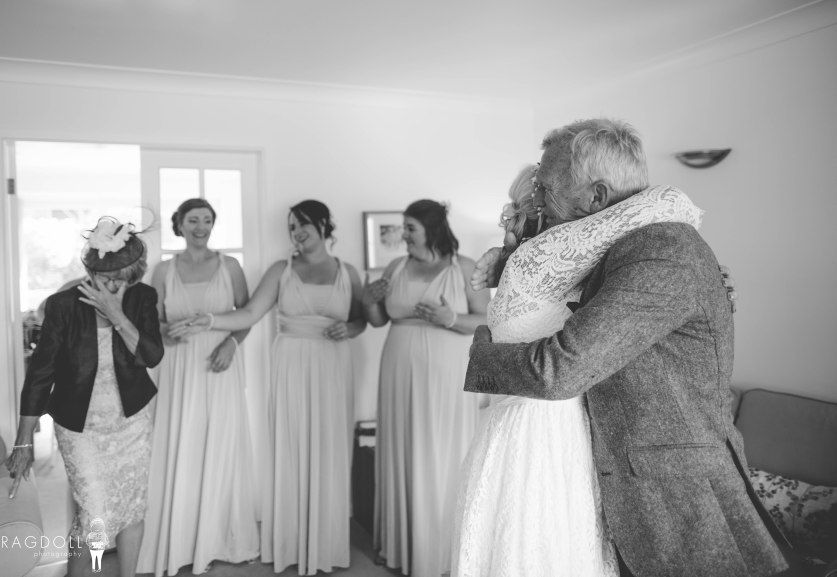 bride hugging father with mum and bridesmaids in the background