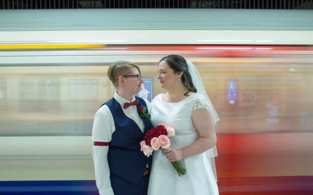 Two brides in London with tube train the background