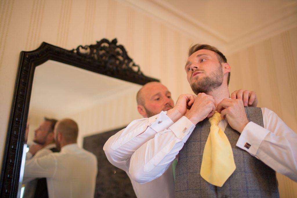 groom having help with tie by best man