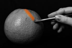 someone is painting an orange without any color with a paintbrush using orange paint meaning you can create your own way of looking at the thing called an orange or your life so yo can discover your ability to start a new beginning