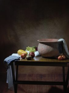 table with bowl, towels tossed about and fruit spread about to indicate a messy kitchen