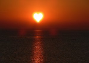 a red sunset of the sea with a white heart in the middle indicating calm and equanimity