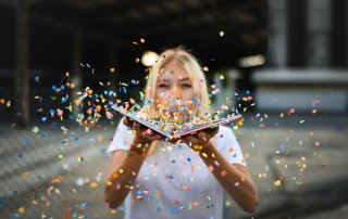 woman blowing a bunch of confetti from the pages of a book symbolizes the notion of flexibility of viewpoint - no one point is the 'truth'