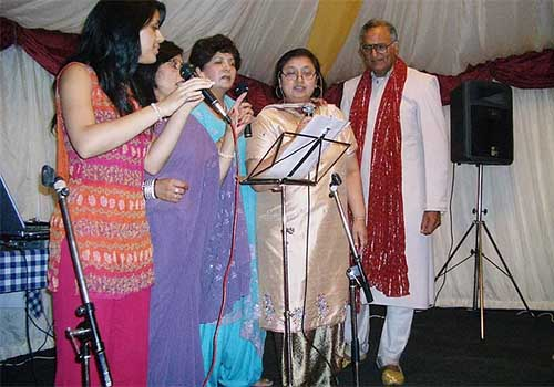 A group of ladies trying their hand at karaoke singing along with Rahi Bains