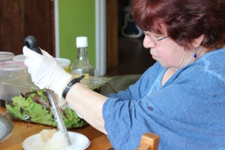 Workshop participant Linda Powell getting hands on, grating parmasean for the chef.