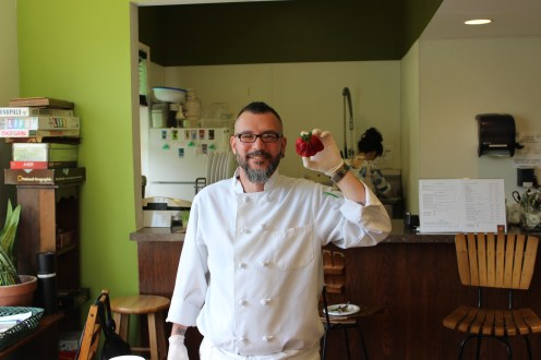 "Chef Enrique displaying an ""ugly fruit"" strawberry."