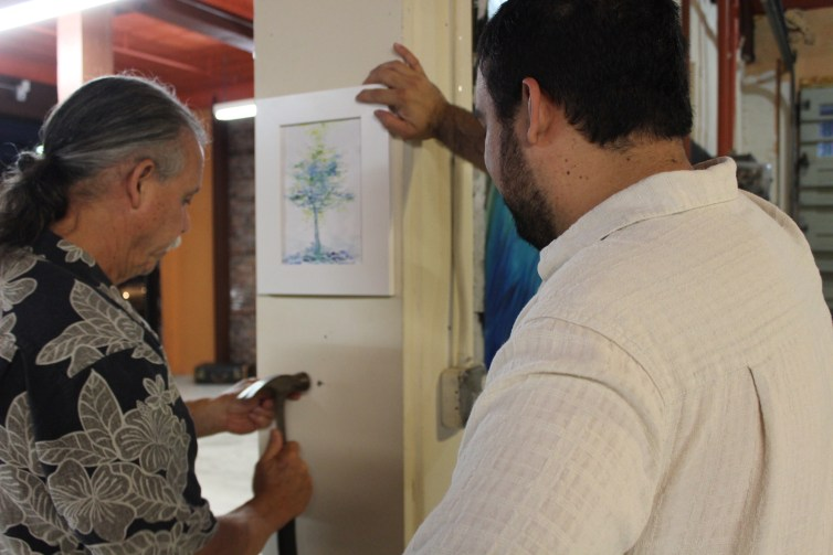 Raíces Director Francisco G. Gómez and his son, artist Gabriel Gómez, setting up the group display for the opening reception.